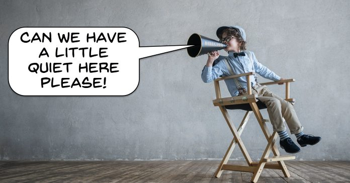Humorous image of child movie director asking for quiet on the set.