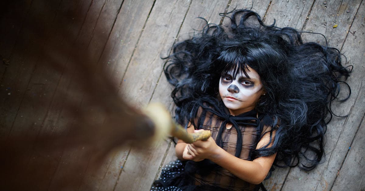 Unusual camera angle on young girl dressed as a witch.
