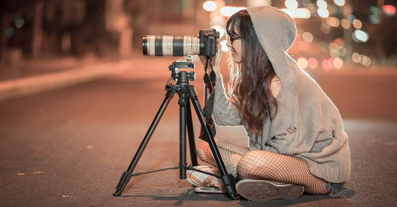 Young woman shooting video at night.