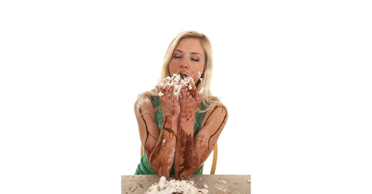 Humorous image woman messily eating cake.