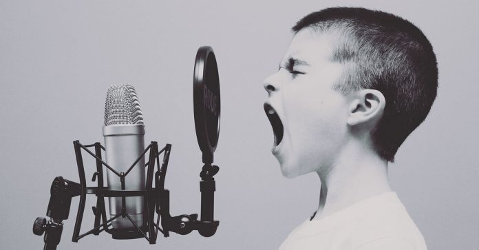 Image of a young boy yelling into a microphone.